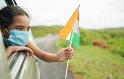 Young girl kid with medical mask holding Indian flag in moving car window - Concept of celebrating Independence or republic day during coronavirus or covid-19 pandemic.