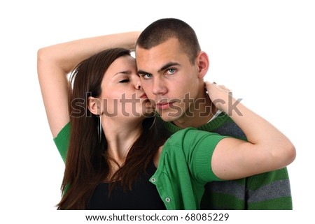Young girl kisses and hugs her boyfriend isolated on white