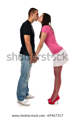 Young girl kisses her boyfriend while holding his hands isolated on white