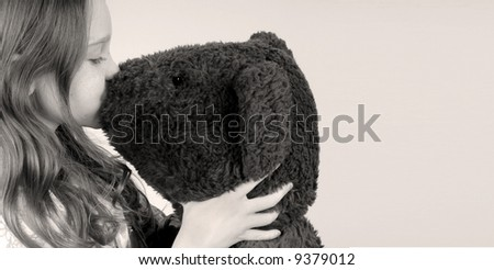 Young girl kissing stuffed toy bear