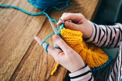 Young girl knitting a circle scarf with yellow and blue coloured yarn. Sitting at the wooden table, close up of the knitting needles.