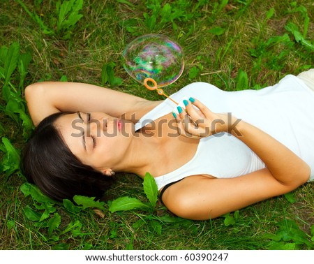 Young girl laying and inflating soap bubbles