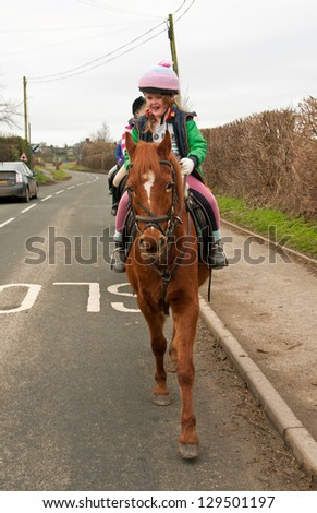 Young girl leading a group of horses down the road