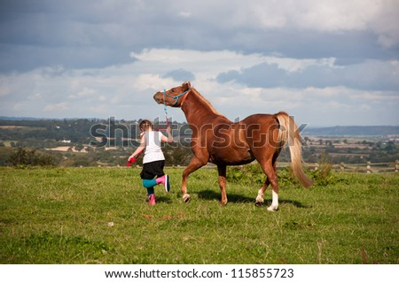 Young girl leading her pony