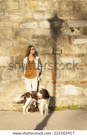 Young Girl Leaning on Brick Wall With Dog Outdoor With Shadow Of Lamp