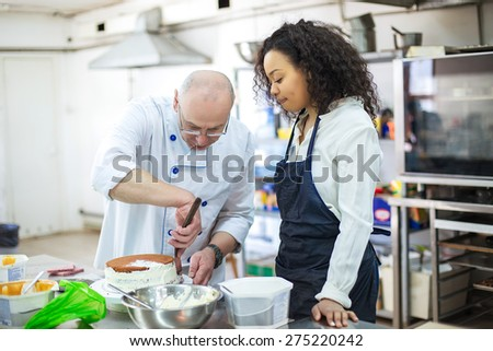 young girl learns to bake cakes with porfessionalnym baker Stock photo ©