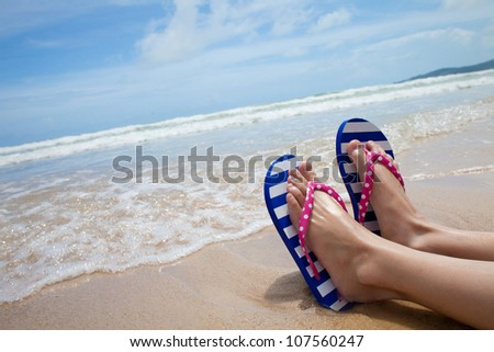 Young girl legs in colorful flipflop sandals on sea beach