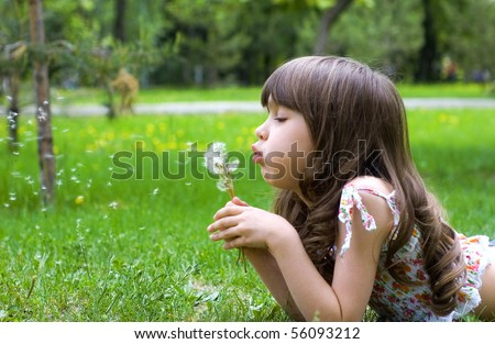 Young girl lies on a grass with dandelions