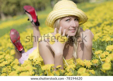 young girl lies on dandelion field
