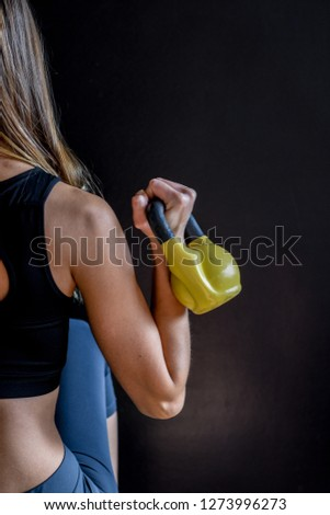 Stock Photo Young girl lifting yellow kettle bell shot from behind in front of a black wall in a gym