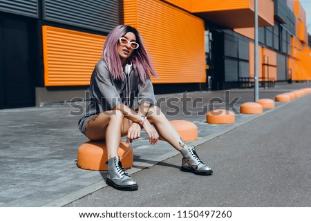 Stock Photo Young girl listening music in headphones, urban street style,outdoor street style hipster dj woman in yellow sunglasses and dj headphones listen music and smile, orange, crazy style, street shoot,