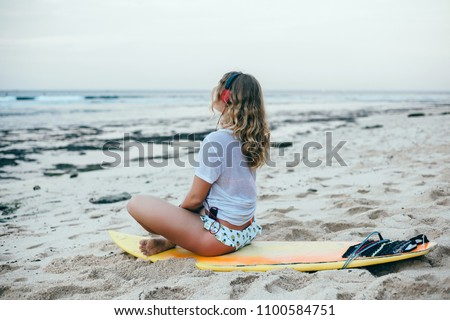 Young girl listening music on the beach, surfing female with yellow surfboard, Bali, freedom, atmosphere, shaka, mp3 player, smartphone, longboard, waves, chill out, sport, sunset