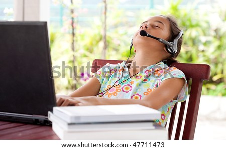 Young girl listening to headphone while on laptop computer, resting her head on chair.