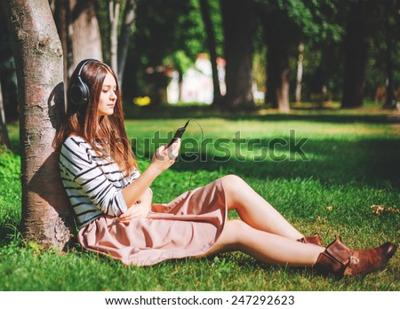 Young girl listening to music in city park