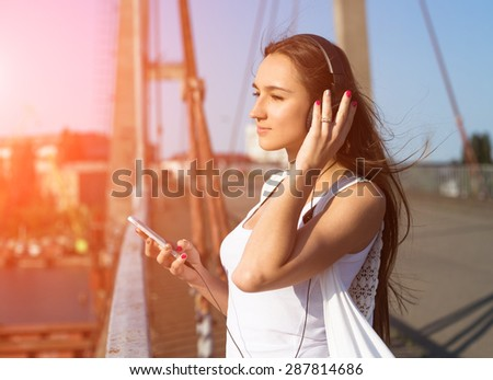 Young girl listening to music in park. Student girl outside listening to music on headphones. Happy young teenager student of Caucasian ethnicity