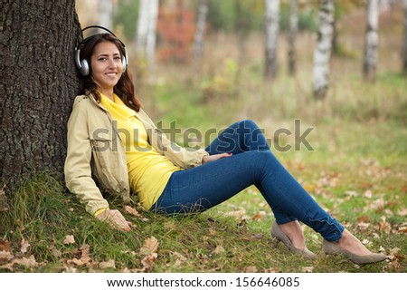 Young girl listening to music on headphones while sitting on grass