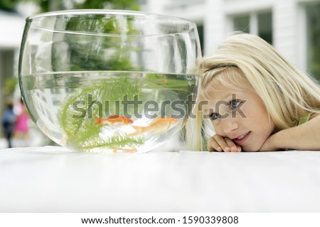 Young girl looking at goldfish bowl outdoors