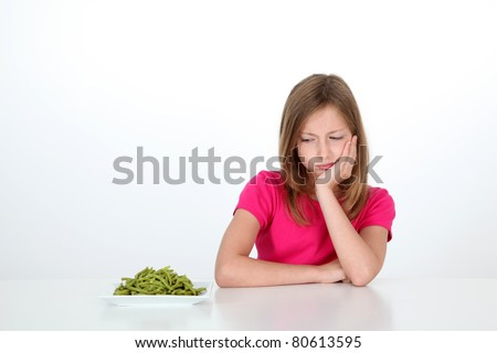 Young girl looking at plate of green beans with disgust