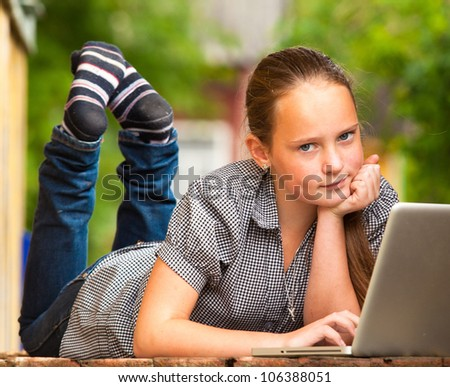 Young girl (looking at the camera) lying on the porch of the rural house with a laptop.
