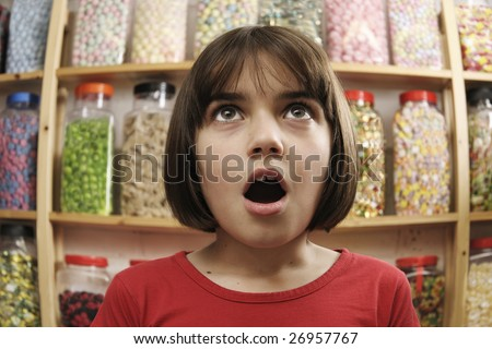 young girl looking in awe at rows of sweets