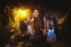 Young girl looking like witch having fun on Halloween in dark room with yellow light and smoke. Teenager in Carnival and Halloween party
