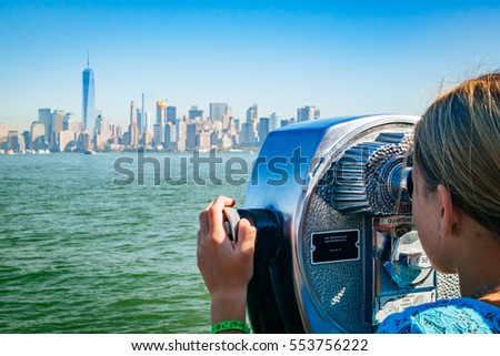 Young girl looking through binoculars at the Manhattan New York City Skyline from Liberty Island. The background shows the lower Manhattan and the financial district, including the Freedom Tower. #553756222
