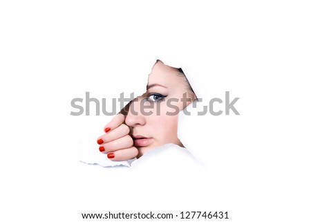 Young girl looking through hole in white paper