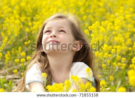 Young Girl Looking to the Heavens in a Field of Yellow Flowers