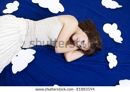 Young girl lying in clouds in studio