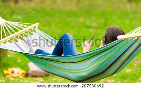 young girl lying on a hammock while using cell phone