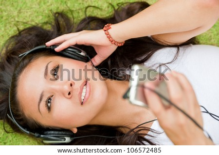 Young girl lying on the grass and listening player - stock photo