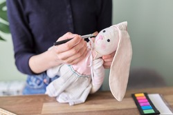 Young girl makes an author's handmade doll bunny, paints her cheeks with cosmetics, hobbies and leisure, mastery concept