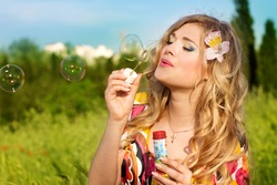 Young girl makes soap bubble