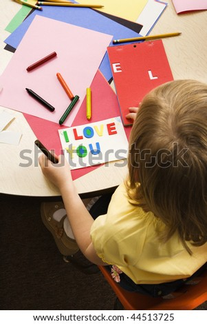 Young girl making card in art class that says I love you. Vertical shot.
