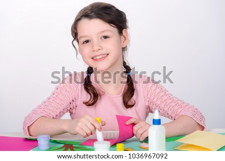 Young girl making craft card. Child cutouts silhouettes from colored paper, arranges pieces and glues them together. #1036967092