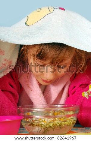 young girl making inhalation over a bowl with steamed camomile water