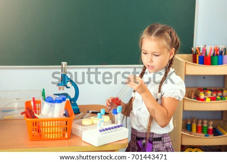 Young girl making science chemistry experiments in school laboratory. Education concept.