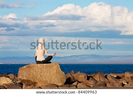 Young girl  meditating by the sea