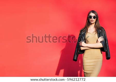 Young girl near the red color wall