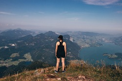 young girl of European descent and in sportswear stands on the edge of the Schafberg rock in Austria near the city of Salzburg. Loving nature. The joy of going down the mountain.