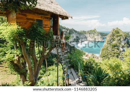 Young girl on steps of traditional house on tree, look at Atun beach, Nusa Penida island. Popular travel destination on Bali holidays. Indonesian background.  travel lifestyle concept