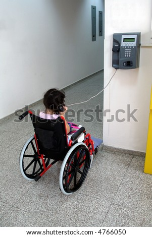 Young girl on wheelchair making a phone call
