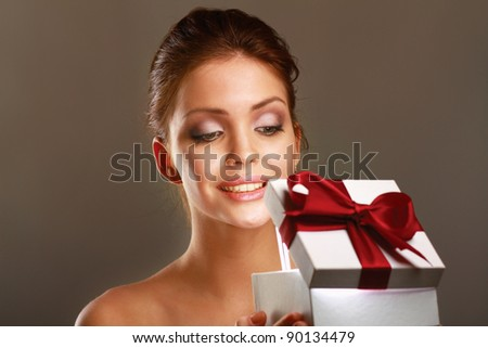 Young girl opening x-mass present isolated on grey background