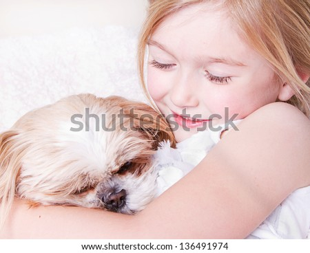 Young girl or child hugging a shih tzu dog