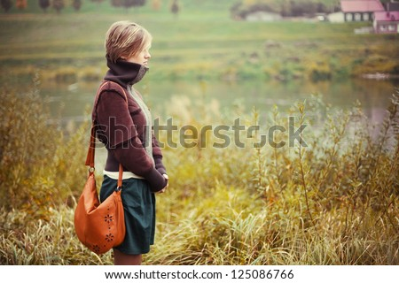 Young girl outdoor spring portrait. Beautiful woman standing and waiting on board of river - stock photo