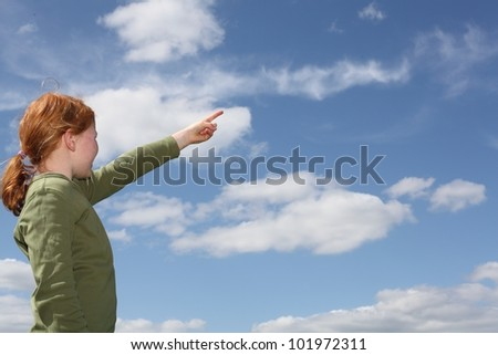 Young girl outside pointing to the sky