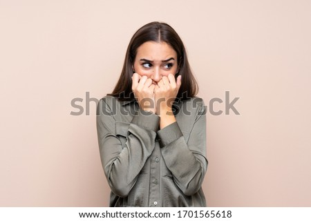 Young girl over isolated background nervous and scared putting hands to mouth ストックフォト ©