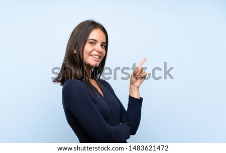 Young girl over isolated blue background pointing finger to the side #1483621472
