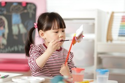 young girl painting hand made craft at home