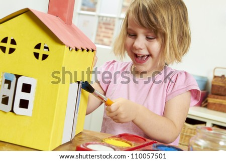 Young Girl Painting Model House Indoors